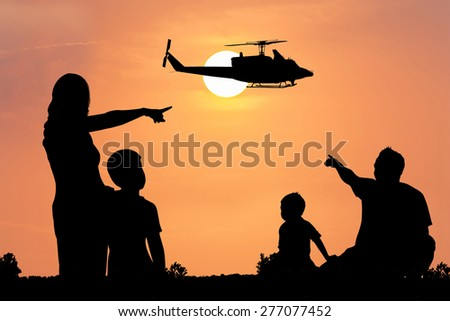 Parents and children look at the helicopter on the sky at sunset - stock photo