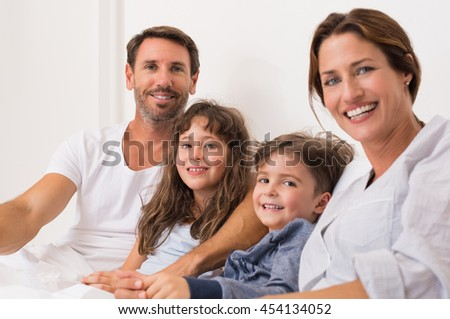 Parents and children lying on bed and having fun together. Happy young family sitting on bed together enjoying. Portrait of a happy family in pajamas looking at camera.