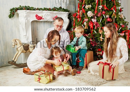 Parents and children sit on rug near Christmas tree, untying ribbons on gift boxes