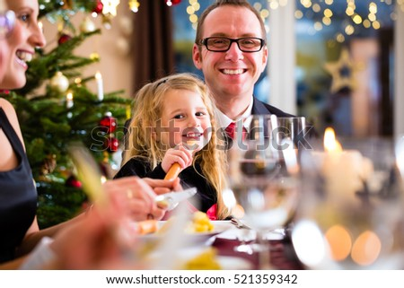 parents and children toasting with wine and water at Christmas eve dinner