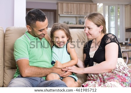 Parents and daughter are enjoying being together at home