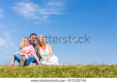 Parents and daughter sitting on grass, total view, centred, centered - stock photo