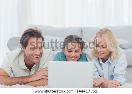 Parents and daughter using a laptop lying on a carpet - stock photo