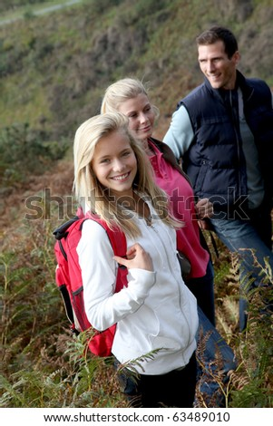Parents and daughter walking in the countryside - stock photo
