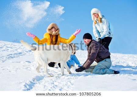 Parents and kids playing with dog in winter park - stock photo