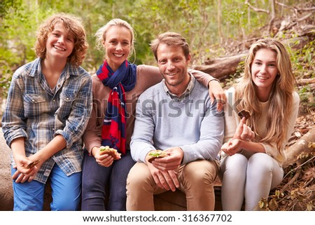 Parents and teenage kids eating outdoors in a forest, portrait - stock photo
