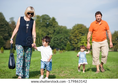 Parents and their children are walking in the park - stock photo