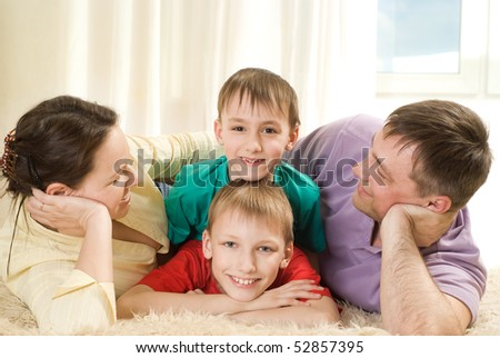 parents and their children lie on the carpet