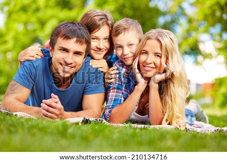 Parents and their children relaxing on grass during summer rest - stock photo