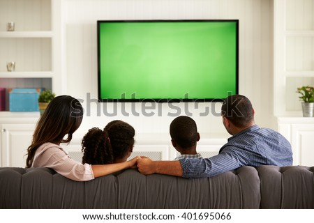 Parents and their two children watching TV together at home - stock photo