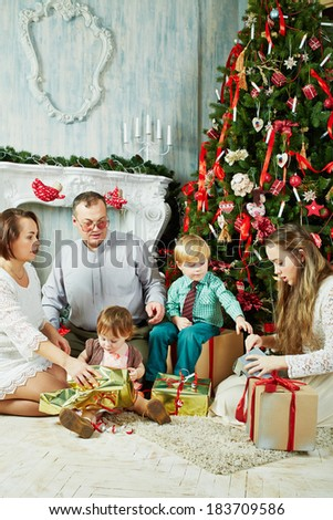 Parents and three their children sit under Christmas tree at room