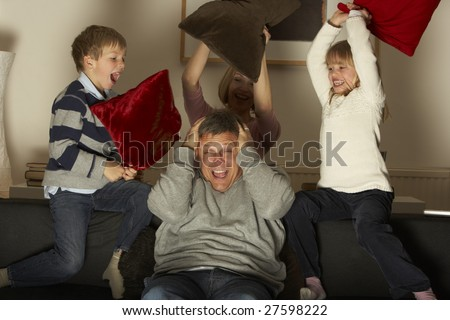 Parents And Two Children In Pillow Fight - stock photo