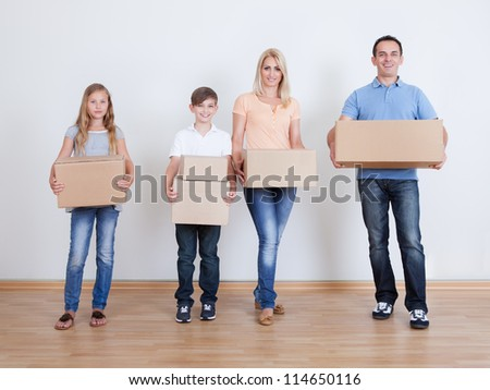 Parents And Two Children With Cardboard Boxes, Indoors - stock photo