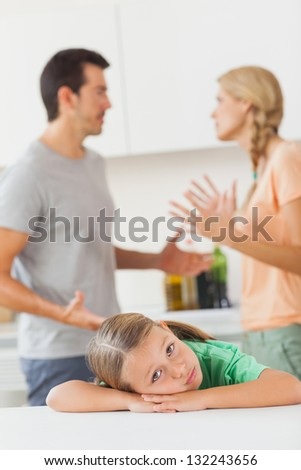 Parents arguing behind a sad girl in the kitchen