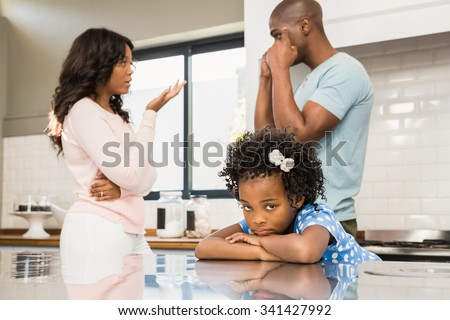 Parents arguing in front of daughter in the kitchen - stock photo