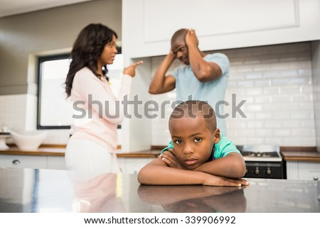 Parents arguing in front of son in the kitchen - stock photo