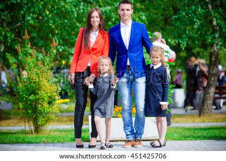 Parents brings theiir little cute daughters to school. Adorable little girls feeling very excited about going back to school - stock photo