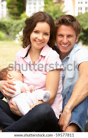 Parents Cuddling Newborn Baby Boy Outdoors At Home - stock photo
