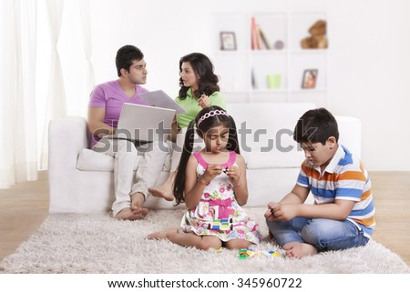 Parents discussing while children play - stock photo