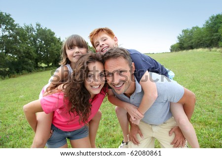 Parents doing piggyback to their children - stock photo