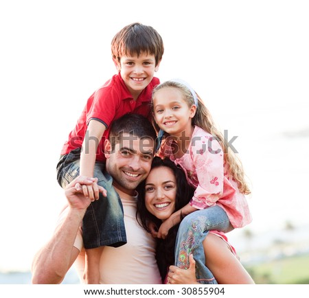 Parents giving children piggyback rides outdoors