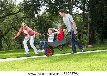 Parents Giving Children Ride In Wheelbarrow - stock photo