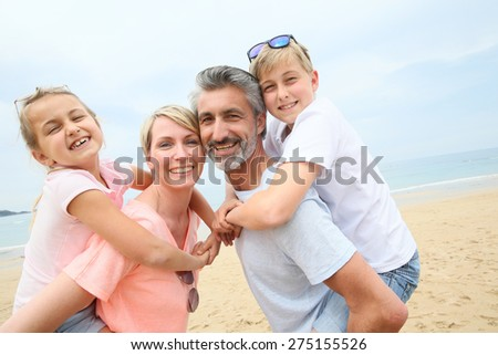 Parents giving piggyback ride to children at the beach - stock photo