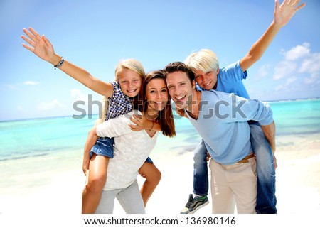 Parents giving piggyback ride to kids at the beach