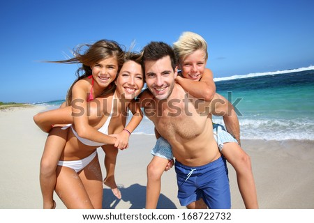 Parents giving piggyback ride to kids at the beach - stock photo