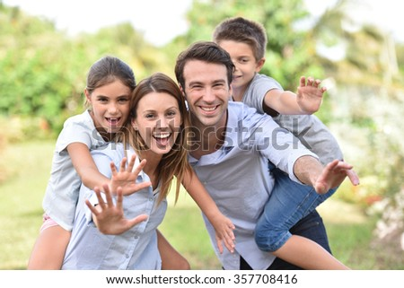 Parents giving piggyback ride to kids outside - stock photo