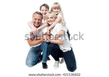 Parents giving piggyback ride to their son and daughter.