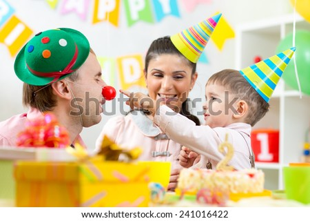 parents have fun celebrating birthday of his kid son - stock photo