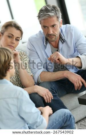 Parents having a talk with teenage boy - stock photo