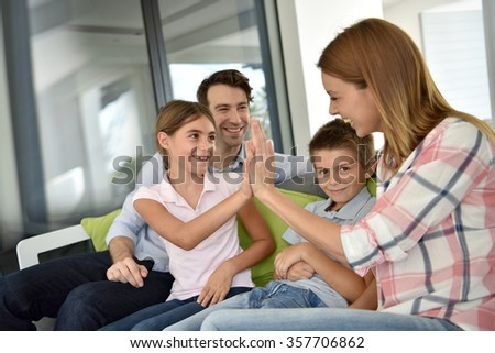 Parents having fun with kids at home - stock photo