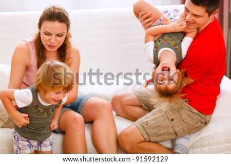 Parents having fun with twins daughters on couch