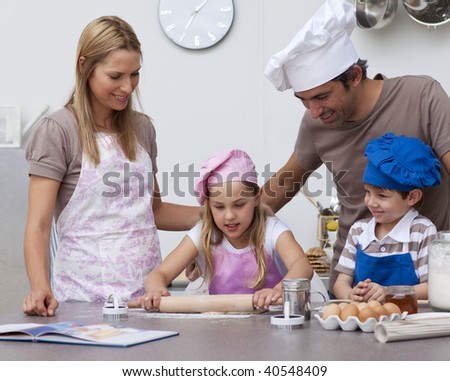 Parents helping children baking cookies in the kitchen - stock photo