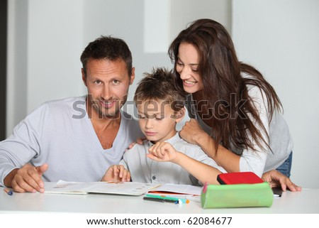 Parents helping son to do his homework - stock photo