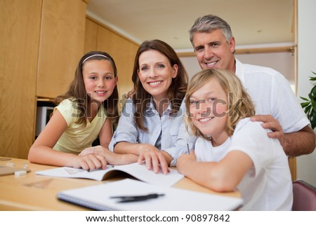Parents helping their children with their homework - stock photo