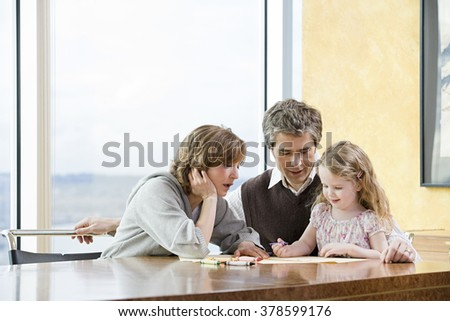 Parents helping their daughter draw - stock photo
