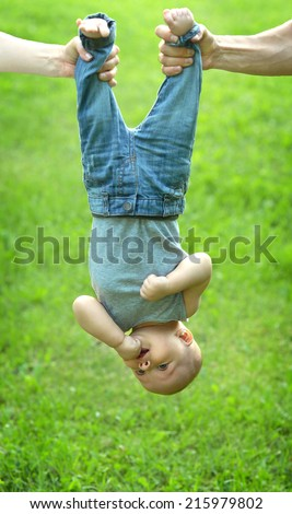 Parents holding little baby upside down outdoor - stock photo