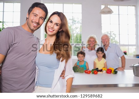 Parents in front of their family in the kitchen - stock photo