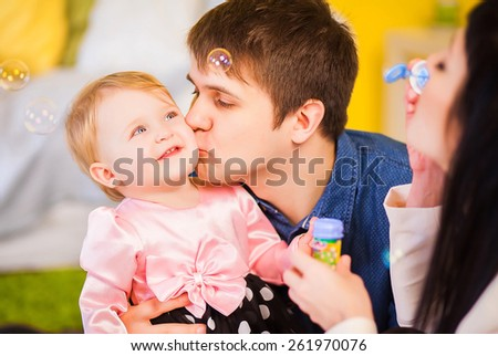 parents inflate little daughter bubbles - stock photo