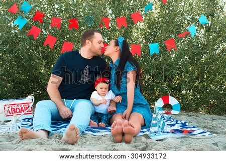 parents kissing behind  their child sitting on the beach - stock photo