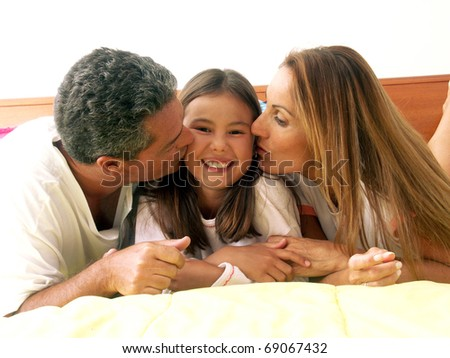Parents kissing their daughter in bed. - stock photo