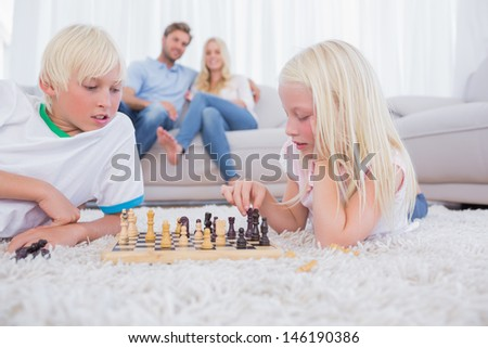 Parents looking at their children playing chess in the living room - stock photo