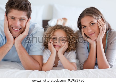 Parents lying on a bed with their son while looking at the camera - stock photo