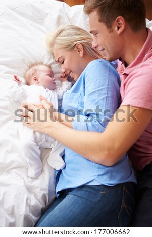 Parents Lying With Baby Girl In Bed Together - stock photo