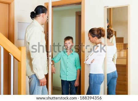 Parents meeting with scold of teenage son in the doorway at home - stock photo