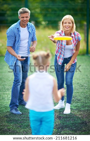 Parents playing frisbee with their daughter - stock photo