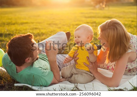 Parents playing with baby in nature at the sunset - stock photo